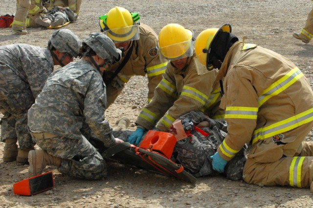 CAMP LIBERTY, Iraq -Sgt. Bridget Cruz-Bianchi (left foreground), from Bainbridge, Ga., and Spc. Kailey Good (left background), from Muncie, In., both combat medics attached to 299th Brigade Support Battalion, 1st Infantry Division, get a long spine board ready as three firefighters from the Victory Base Complex Fire Dept. prepare to log roll a casualty for transport to the closest troop medical center during a March 6 MASCAL exercise.