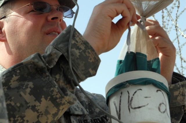 VICTORY BASE COMPLEX, Iraq -Staff Sgt. Seth Odette, 1848th Medical Detachment's preventative medicine section, removes the collecting unit from a Center for Disease Control miniature light trap. The trap uses an ultraviolet light and a small fan to trap mosquitoes, sand flies and other flying insects.