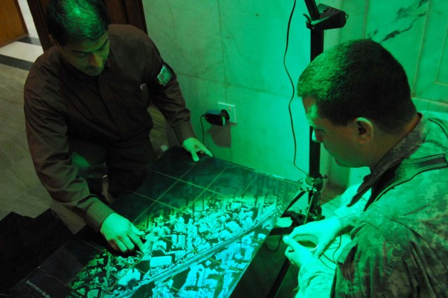 Victor Villavicencio, liaison, Army G2, demonstrates the benefits of holographic imaging technology to Capt. Norman Adamson, Joint Headquarters Army Advisory Transition Team during the Iraq Assistance Group conference on Feb. 20 at Al Faw Palace.  This image, which shows a three dimensional representation of Baghdad, is provided to units as theater provided equipment through the Tactical Battlefield Visualization project.