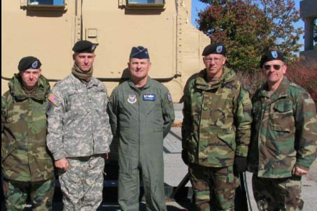 Staff Sgt. James Jett, safety NCO for the Army Safety Augmen-tation Division, U.S. Army Garrison Safety Office (second from left), stands in front of the HMMWV Egress Assistance Trainer at the 2005 U.S. Army Forces Command's Commanders Conference. Jett played an instrumental role in the creating the device.