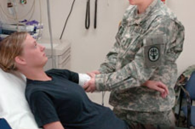 Sgt. Chelsey Billing, DeWitt Army Hospital emergency room NCO, checks a patient's blood pressure as part of her duties.