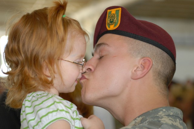Spc. Andy Cogswell, a military policeman with the 65th Military Police Company, kisses his daughter for the first time in 15 months Saturday at Green Ramp on Pope Air Force Base. The company of 160 Soldiers was welcomed home by Family and friends after a 15-month deployment in Iraq.