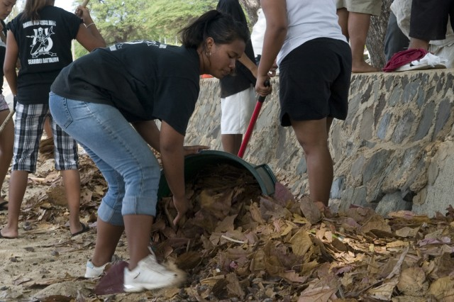 JROTC cadet Ester Wells sweeps up a pile of leaves at the Pililaau Army Recreation Center, Friday. Logan and more than 20 of her fellow Waianae High School JROTC cadets volunteered for the clean up to provide a safe beach environment for the military ohana.