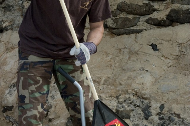 Master Sgt. John Keawe, 1101st Garrison Support Unit, sweeps the beach clean of debris during a beach clean up, Friday.""