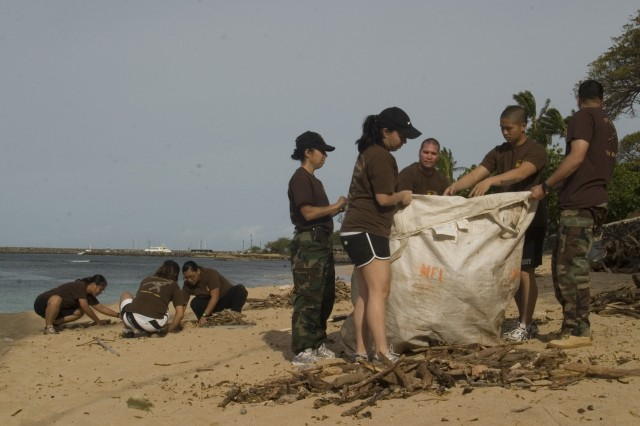 """Soldiers from the 1101st Garrison Support Unit and JROTC cadets pick up driftwood and debris during a beach clean up at Pililaau Army Recreation Center, Friday. The volunteer effort brought more than 50 Soldiers and JROTC cadets together to preserve the beauty of the land surrounding the center."""""""