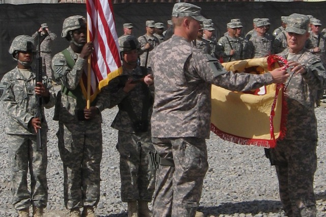 143d Expeditionary Sustainment Command color guard Soldiers Staff Sgt. Roya S. Taylor, Sgt. Clifton Smith, Spc. Johnathan R. Brown and Sgt. David Wilborn, observe as Command Sgt. Maj. Michael D. Schultz and Brig. Gen. Daniel I. Schultz uncase the 143d's colors during a ceremony outside its headquarters at Kandahar Airfield, Afghanistan March 5, 2009.