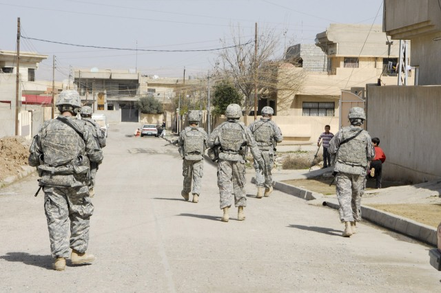 Several Soldiers with Battery B, 2nd Battalion, 82nd Field Artillery Regiment., 3rd Heavy Brigade Combat Team, 1st Cavalry Division, walk along an urban street in 7 Nissan, a neighborhood in northern Mosul. This and other streets like it in the area are part of a series of projects organized by the city's residential, government and military leaders to clean its streets of trash and debris. A month ago, the curbsides and empty lots along this street were riddled with household garbage.
