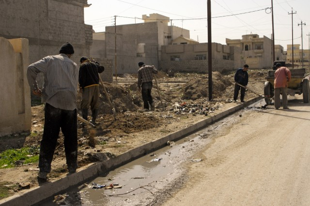 A group of men that live in 7 Nissan, a neighborhood in northern Mosul, shovel the trash that has accumulated in empty lots and along curbsides. 7 Nissan and many neighborhoods in Mosul are part of a series of projects devoted to cleaning the city's streets, providing employment for its residents and morale in its communities.