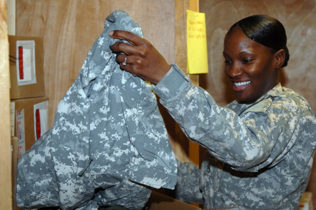 BAGHDAD- Staff Sgt. Dawn Coleman, supply sergeant for Company A, Division Special Troops Battalion, 1st Cavalry Division, opens a shipment for a Soldier from the Army Direct Ordering program at Camp Liberty, March 13.