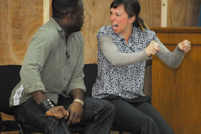 "Kyle Terry, left, and Amber Kelly, both actors with the show ""Sex Signals,"" demonstrate the importance of good communication during a performance at Camp Victory, Iraq, March 11.  ""Sex Signals"" is a program aimed at helping prevent"