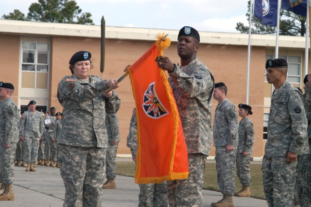 Maj. Gen. Susan Lawrence and Command Sgt. Maj. Donald Manley, NETCOM/9th SC (A) commanding general and command sergeant major, unfurl the new colors of the 7th Signal Command (Theater) during an activation ceremony March 6, at Fort Gordon, Ga.