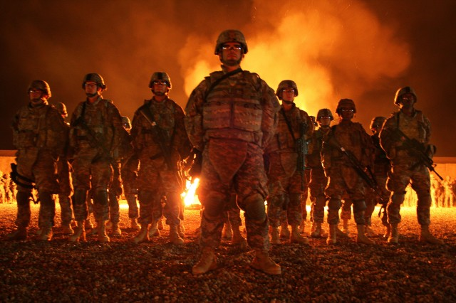 A bonfire lights the sky as noncommissioned officers from the 172nd Infantry Brigade welcome 22 graduates of the Blackhawk Warrior Leader Course into the leadership ranks at Forward Operating Base Kalsu, Iraq, March 7, 2009.