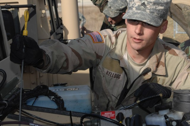 CUTLINE OIL: Sgt.  Jason Kellogg, Company B, 193rd Brigade Support Battalion, checks the oil on a new vehicle assigned to the  4th MEB, March 5.