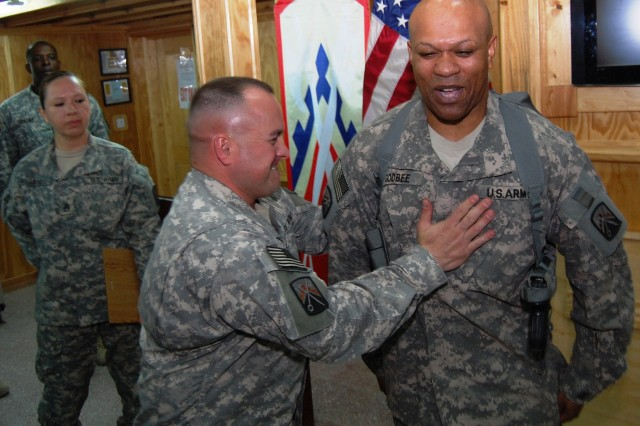 Command Sgt. Maj. James Spencer, command sergeant major, 16th Sustainment Brigade, welcomes incoming Command Sgt. Maj. Johnny Godbee, command sergeant major, 16th Special Troops Battalion, 16th Sust. Bde., into the fold during a frocking ceremony in the brigade's tactical operations center at Contingency Operating Base Q-West March 13, 2009.  (U.S. Army photo by Sgt. Keith M. Anderson)