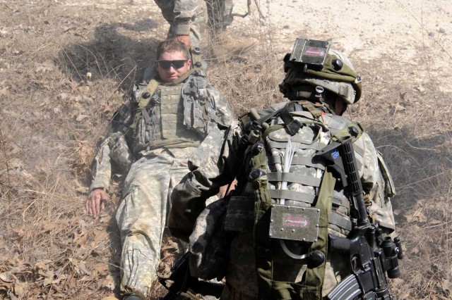 """A Paratrooper from Company D, 1st Battalion, 325th Airborne Infantry Regiment, 2nd Brigade Combat Team, 82nd Airborne Division, drags Spc. Jacob Rutledge, an Arlington, Wash., native, to safety after he was """"notionally"""" shot during the brigade-wide mission readiness exercise."""