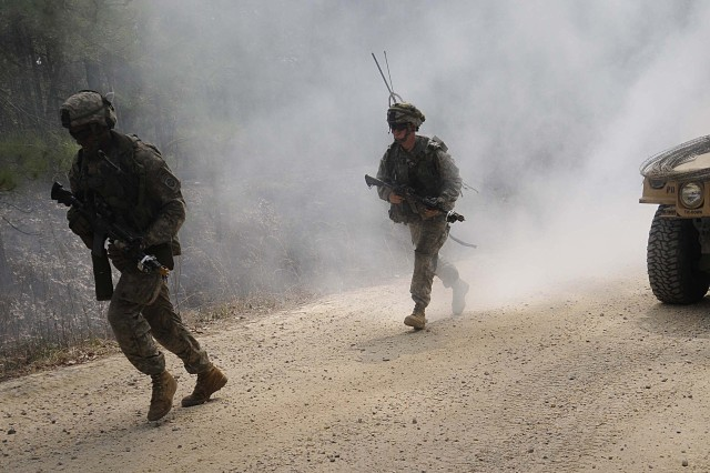 Two paratroopers from Company D, 1st Battalion, 325th Airborne Infantry Regiment, 2nd Brigade Combat Team, 82nd Airborne Division, run through the smoke to get close to their objective during the brigade-wide mission readiness exercise. The MRE is the brigade's quick reaction force validation exercise.