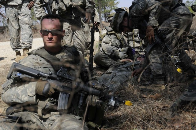 """Paratroopers from Company D, 1st Battalion, 325th Airborne Infantry Regiment, 2nd Brigade Combat Team, 82nd Airborne Division, wait to be evaluated by a medic after they were """"notionally"""" wounded in action during the brigade-wide mission readiness exercise. The MRE is the brigade's validation of their quick reaction force capabilities."""