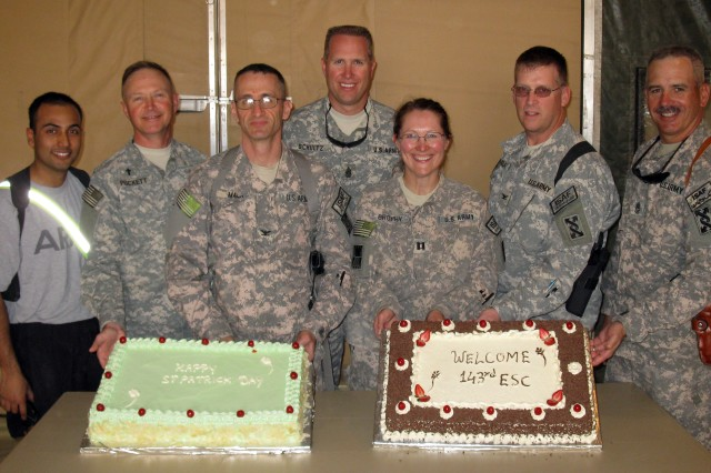 During the 143d Expeditionary Sustainment Command's St. Patrick's Day party Sunday; 1st Lt. Sharif I. Faruque; Col. Stanley Puckett; Col. Michael A. Mann; Command Sgt. Maj. Michael D. Schultz; Capt. Anne K. Brophy; Col. Andrew M. Barclay and Sgt. Maj. Thomas Curran display cakes decorated in honor of both St. Patrick's Day and the 143d's recent arrival here to Kandahar Air Field, Afghanistan.