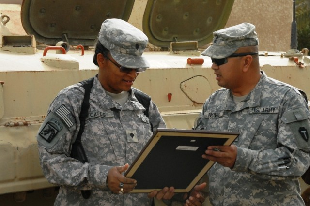 BAGHDAD - Spc. Verna Oates (left), from Texarkana, Texas, serving with Headquarters and Headquarters Company, 56th Infantry Brigade Combat Team, 36th Infantry Division, Multi-National Division-Baghdad, receives a framed copy of the Non-Commissioned Officer's Creed from 1st Sgt. Ron Novio, senior enlisted leader for HHC, 56th IBCT, during a promotion ceremony held at Camp Victory on March 14. Oates, promoted under the battle field promotion system which selects deserving, eligible Soldiers for promotion to either sergeant of staff sergeant, served for nine years on active duty, with nearly seven years in Germany. Following a break in service, Oates joined the Texas National Guard in July 2001 and is now serving in her second tour to Iraq in support of Operation Iraqi Freedom.