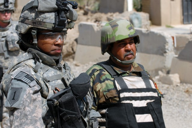 BAGHDAD - Philidelphia native, Spc. Tymara Burnley (left), a medical logistics specialist with 299th Brigade Support Battalion, stands guard with an Iraqi Army soldier during a public works sub-station transfer ceremony at Yarmouk in the Mansour district March 16.