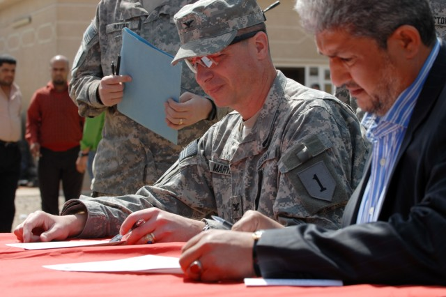 BAGHDAD – Col. Joseph Martin (left), commander, 2nd Brigade Combat Team, 1st Infantry Division, signs the transfer documentation that officially hands over four Coalition funded public works sub-stations to the Government of Iraq with the deputy mayor of Baghdad, Naeem Abaob al-Kaabi, at Yarmouk in the Mansour district March 16.