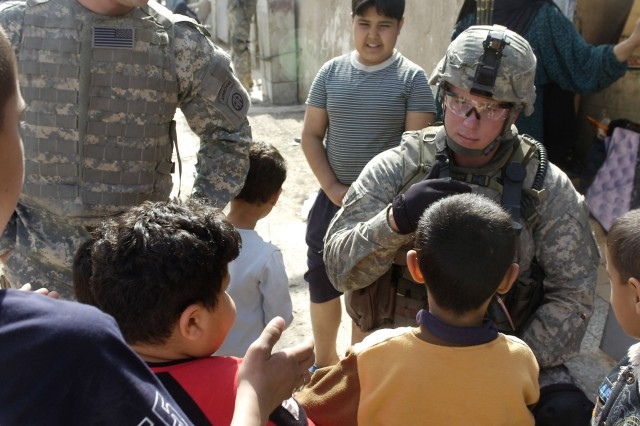 BAGHDAD - Spc. John Young, a native of Durham, N. C., assigned to Troop C, 5th Squadron, 73rd Cavalry Regiment, greets some Iraqi children during a combined foot patrol in Baghdad's Rusafa district March 7 with National Police officers from the 3rd Battalion, 8th NP Brigade, 2nd NP Division.