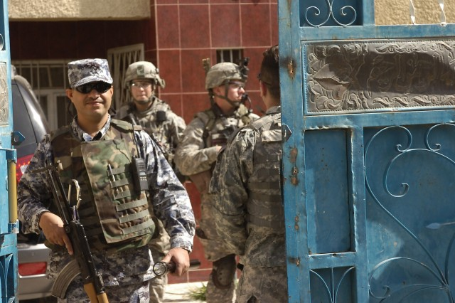 BAGHDAD - National Police Officers assigned to the 3rd Battalion, 8th NP Brigade, 2nd NP Division and paratroopers assigned to Troop C, 5th Squadron, 73rd Cavalry Regiment, walk out of a residence after inspecting it during a Iraqi-led clearance operation March 7 in the Rusafa district of eastern Baghdad.