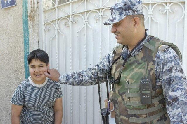 BAGHDAD - A National Police Officer assigned to the 3rd Battalion, 8th NP Brigade, 2nd NP Division pinches a boy's check after clearing a house March 7 in the Rusafa district of eastern Baghdad.