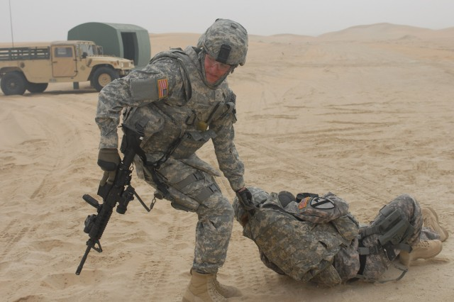 """CAMP BUERHING, Kuwait - Detroit, Mich. Native, Pvt. Matthew Osborne, a gunner from 1st Brigade Special Troops Battalion, 1st Brigade Combat Team, 1st Cavalry Division, drags a """"wounded"""" troop to an established casualty collection point to further assess him during the personal security detachment training in Kuwait."""