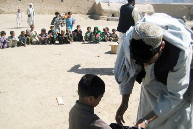 Afghan children sit in a circle as they wait for a village elder to size them for shoes in southern Afghanistan village, March 4, 2009. U.S. Soldiers also delivered soccer balls, footballs and other toys for the children.