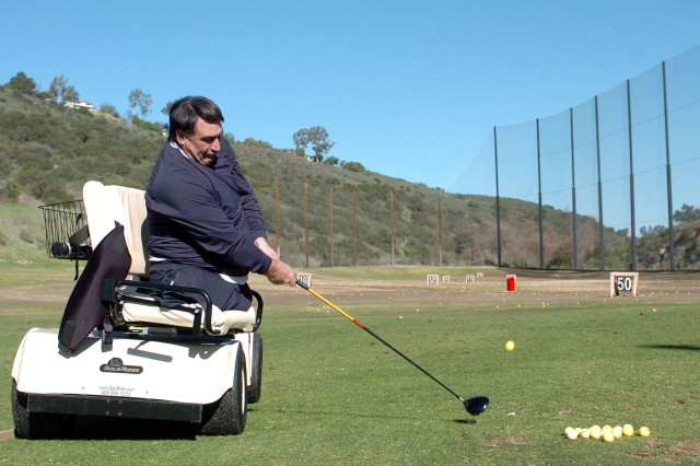 First Swing instructor Marty Ebel demonstrates how to drive a golf ball from a specialized cart during a golf clinic for wounded warriors on the driving range at Admiral Baker Golf Course in San Diego. The next stop on the tour is March 22-23 at Fort Belvoir, Va.