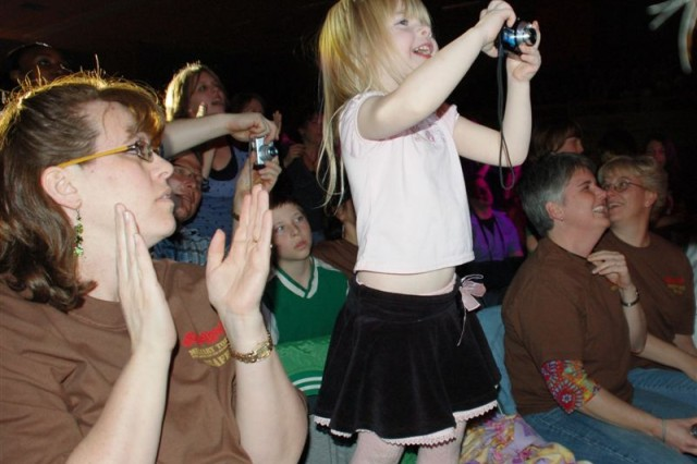 Little Amina, daughter of Family Member Jill Norris, helps lead a crowd of over1,800 taking pictures of a dazzling performance by Sugarland and two other award winning country music bands at the Sporthal Rumpen in Brunssum, Netherlands, March 13. The only thing that out-flashed the amateur photographers was the performance itself, which dazzled a crowd multi-national crowd.