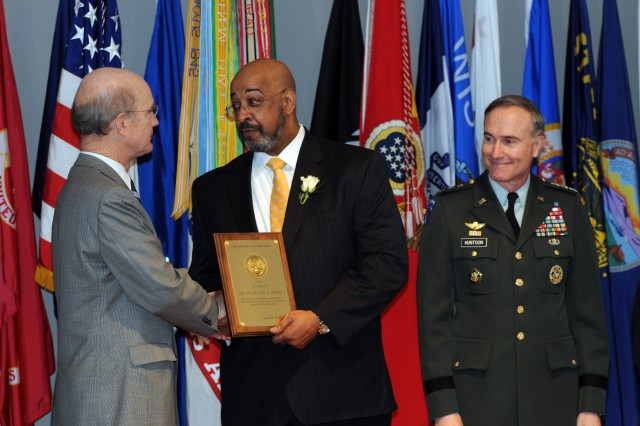 Secretary of the Army Pete Geren presents the Award for Outstanding Achievement in Equal Employment Opportunity to Spurgeon A. Moore, director, Equal Employment Opportunity Compliance and Complaints Review Directorate, during the 2008 Secretary of the Army Awards ceremony at the Women in Military Service to America Memorial, March 18.  Moore received the award in part because his leadership increased the quality and efficiency of the complaints program while enhancing communication and cooperation between all levels of the Army Equal Employment opportunity community.