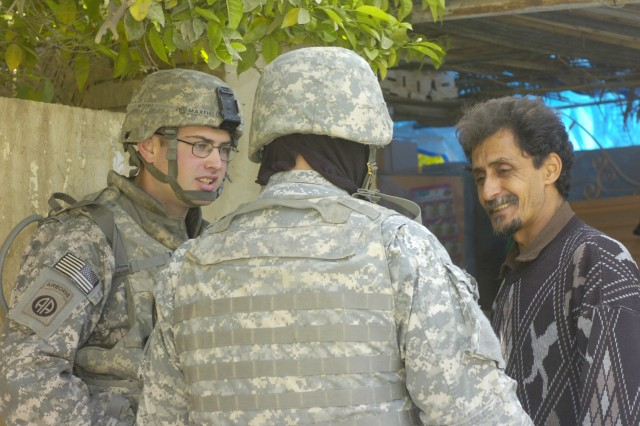 BAGHDAD - Oak Hill, Va. native, 1st Lt. Daniel Maxfield (left), a Military Police platoon leader assigned to the Brigade Special Troops Battalion, 3rd Brigade Combat Team, 82nd Airborne Division, Multi-National Division-Baghdad, speaks with a local shop owner in the neighborhood of Beladiyat March 16, during a foot patrol in the 9 Nissan District of eastern Baghdad.  Maxfield, along with MP paratroopers patrol the areas surrounding Joint Security Station Loyalty to check for signs of insurgent activity and talk to the locals.