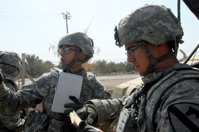 CAMP SLAYER, Iraq -Spc. Steven Richard (left), an infantryman from Plano, Texas, and Spc. Chris White, infantryman from Austin, Texas,  both with 2nd Battalion, 8th Cavalry Regiment , 1st Brigade Combat Team, 1st Cavalry Division, compare notes on points of interest and discuss area characteristics from a command point before dividing up to search for caches during a March 10 exercise.