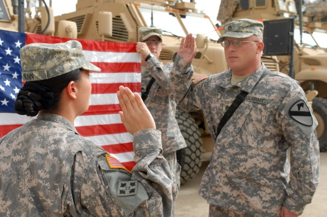 "CAMP WAR EAGLE, Iraq - Puyallup, Wash. native , Capt. Olivia Nunn (left), commander, Headquarter and Headquarters Troop, 1st ""Ironhorse"" Brigade Combat Team, 1st Cavalry Division, precedes over Cuba, Miss. Native,  Staff Sgt. Christopher Carter's reenlistment service March 13.  Carter is a Bradley fighting vehicle commander for the ""Ironhorse"" Brigade and has pledged to finish a 20 year career in the Army."