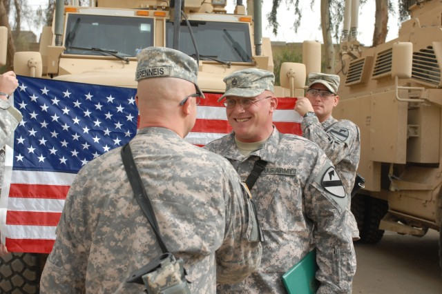 CAMP WAR EAGLE, Iraq -  Wuerzburg, Germany native,  Sgt. 1st Class Marcel Brenneis (left), operations noncommissioned officer, 1st Brigade Combat Team, 1st Cavalry Division, congratulates Cuba, Miss. Native, Staff Sgt. Christopher Carter (right), a Bradley fighting vehicle commander, on his re-enlistment  March 13.