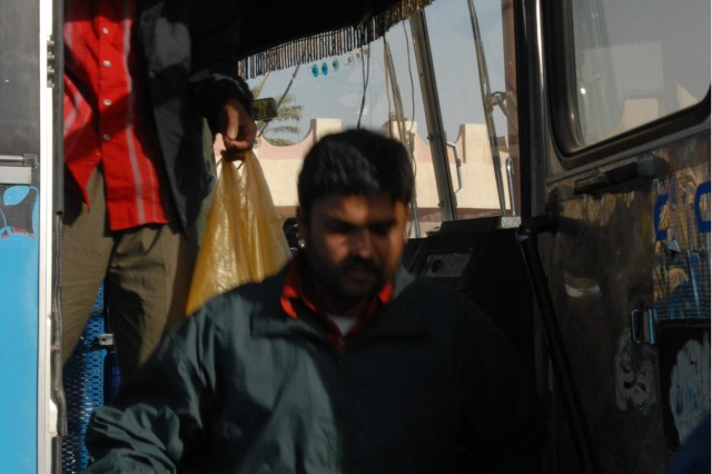 TARMIYAH, Iraq - Two former detainees offload their bus March 16 after traveling from a detention facility to Bukhari Hall in Tarmiyah. The two men and 13 others were part of Operation Forgiving Associator, where Soldiers of 1st Battalion, 111th Infantry Regiment, 56th Stryker Brigade Combat Team released them in conjunction with the Security Agreement. Under the agreement, detainees with active warrants for crimes are turned over to the Iraqi Police, and detainees without warrants are returned to their families.