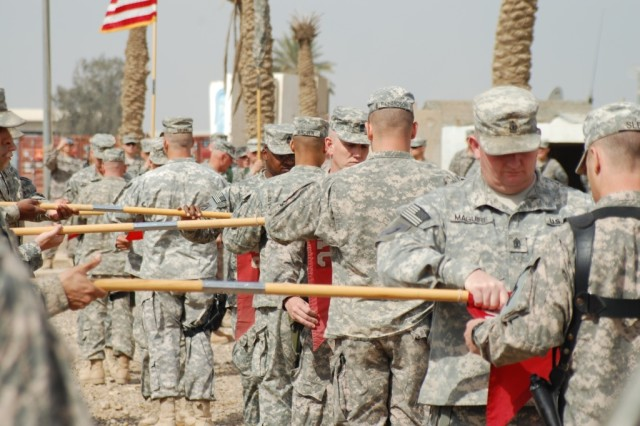 CAMP LIBERTY, Iraq - Soon to be departing theater, company commanders and first sergeants of the 890th Engineer Battalion, from Gulfport, Miss., case their guidons during the transfer of authority ceremony on March 18, in front of the battalion tactical operation center on Camp Liberty, Iraq.