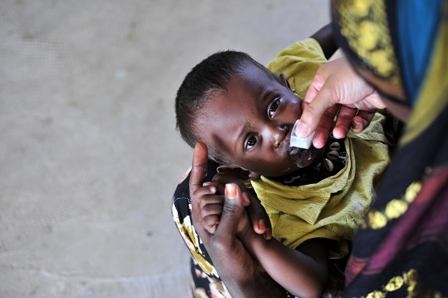 A mother in the village of Hanley II, Djibouti, gives her child a dose of Albendazole, a de-worming medication provided to her by servicemembers from the Combined Joint Task Force-Horn of Africa during a Medical Civil Action Project March 8.