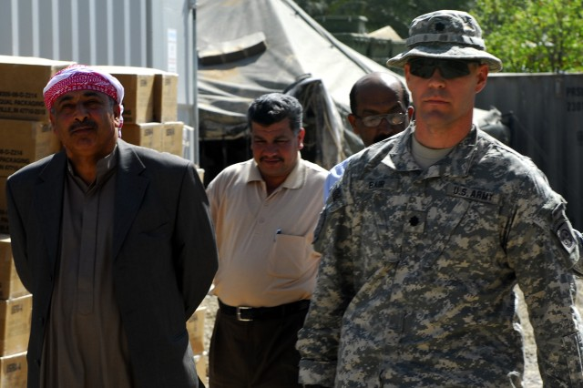 Mr. Mustat (left), a local Sons of Iraq (SoI) leader walks with Lt. Col. Dave Bair (right), commander, 1st Battalion, 505th Parachute Infantry Regiment, after discussing the continued presence of the SoI program and security improvements in the Rashid District of Baghdad at Joint Security Station Zubaida March 12.
