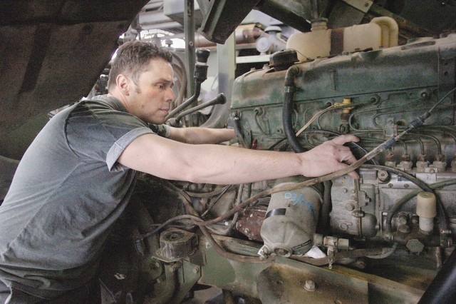 David Cooper, heavy wheel mechanic works on a see tractor that was brought in for repairs. The tractor made in Germany is versatile bue requires skill to repair.