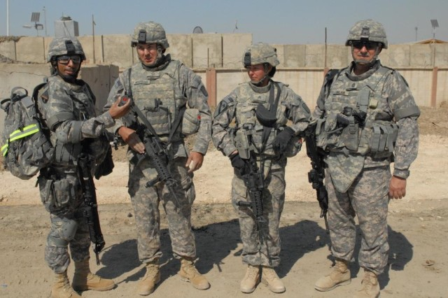 BAGHDAD - Brig. Gen. Owen Monconduit (far left), commander of the 225th Engineer Brigade, 1st Cavalry Division, Multi-National Division-Baghdad stands with Command Sgt. Maj. Joe Major (far right) to present his coin of excellence to Pfc. Jason Bradshaw (middle left) at Joint Security Station Ur in northeast Baghdad, March 17.  Bradshaw, from Rolla, Mo., and his non-commissioned officer, Sgt. Natalia Tharp (middle right), from Canajo Lane, N.Y.,  have been working at JSS Ur for the past week with the 46th Eng. Battalion,  installing screens around the entire station to help mitigate threats to the Soldiers living inside.