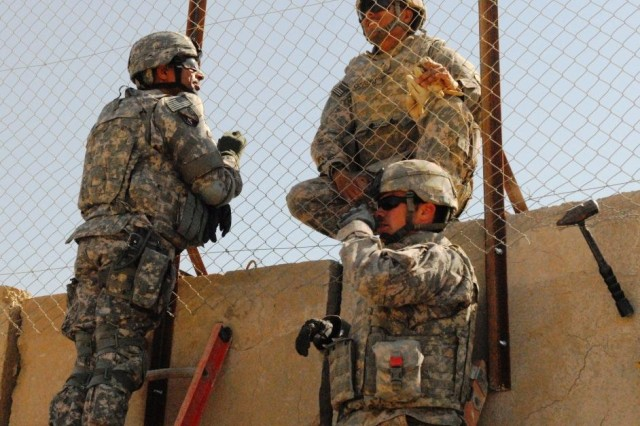 BAGHDAD - Pineville, La. native, Brig. Gen. Owen Monconduit (right), commander, 225th Engineer Brigade, discusses the screen construction progress with  two Soldiers from the 46th Eng. Battalion, Sgt. Michael Sones, and Pfc. Santos Comacho.  Sones, from Dallas and Santos, from Pleasanton, Texas, have been working for the last week on installing screens around the entire parameter of Joint Security Station Ur in northeast Baghdad to increase the compound's defenses against terrorist attacks.