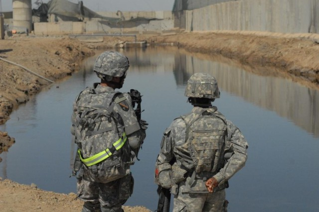 BAGHDAD - Pineville, La. native, Brig. Gen. Owen Monconduit (left), commander, 225th Engineer Brigade, and 1st Lt. Kewanda Tate of Company A, 46th Eng. Battalion, who hails from Tuscaloosa, Ala., discuss the newly completed drainage pond March 17 at Joint Security Station Ur located in northeast Baghdad.  The drainage pond was constructed by engineers from the 46th Eng. Bn. to alleviate the ongoing flooding problem at JSS Ur.