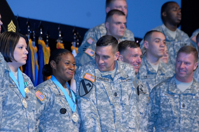Combined Arms Center Command Sgt. Maj. Philip Johndrow squeezes in next to new Sergeant Audie Murphy Club inductee Staff Sgt. Brenda Reed-Miller at the conclusion of the dual SAMC and NCO induction ceremony March 17 in Eisenhower Auditorium.