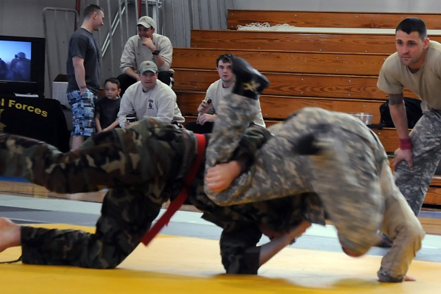 Maj. Brian Ducote from Fort Leavenworth and Staff Sgt. Ryan Kraeger from Fort Riley are judged by Staff Sgt Brandon Brewer as they compete in the light heavyweight finals during the combatives tournament March 14 at Harney Sports Complex.