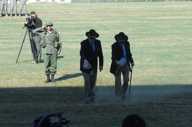 CSM(R) Basil Plumley and LTG(R) Hal Moore sprinkle soil from LZ X-Ray, while a period Vietnam War Soldier salutes in the background during the Sacred Soil Ceremony Thursday on the parade field.  Moore and Plumley were the battalion commander and command sergeant major of the 1st Battalion, 7th Cavalry Regiment, that fought the first major conflict of the Vietnam War.  It was made into the movie We Were Soldiers.