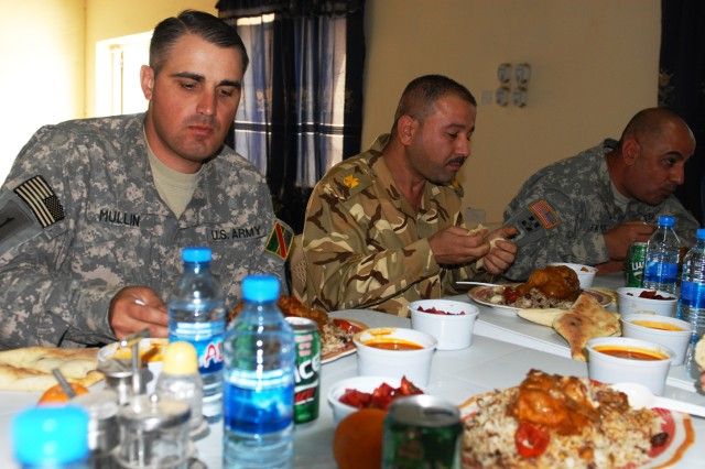"BAGHDAD - Maj. Jim Mullin (left), team chief, Team Weasel, 6th IA Div. MiTT, eats a traditional meal with his Iraqi counterparts at JSS Salam. ""We live with our guys, sometimes we eat with them, we go on missions with them,"" he said. ""If this base had anything happen to it, we're under the same circumstances as they are operating under."""