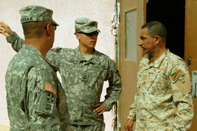 BAGHDAD – Master Sgt. Michael Eddy (center), non-commissioned officer in charge, Team Weasel, 6th IA Div. MiTT, speaks with Sgt. Major Ayad Mohammed Ali Jassem, Intelligence, Surveillance and Reconnaissance Battalion, 6th ID Div. with the help of an interpreter. Eddy, from Enfield, Conn., works primarily with the ISR Bn. of the 6th IA Div.